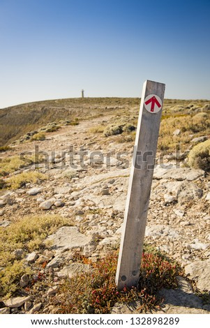 Arrow on signpost points the direction along the cliffs to the distant lighthouse - stock photo