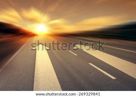 arrow on the road with sunset sunrise on horizon  - stock photo
