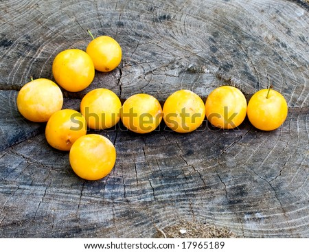 arrow pointing left made with yellow plums on wood surface - stock photo