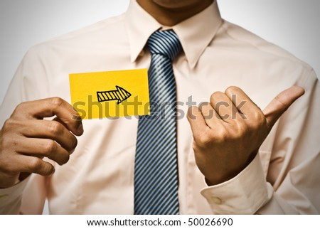 Arrow shape on yellow card and hand gesture by businessman. - stock photo