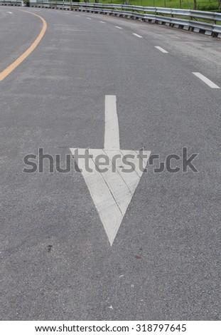 Arrow sign on asphalt surface  - stock photo