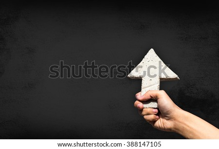 Arrow sign on man hand; business concept on dark cement background  - stock photo