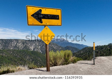 Arrow sign on top of high altitude cliff This is an image of a large arrow sign on top of a high altitude cliff warning traffic of a deep ravine. - stock photo