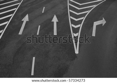 Arrow signs and other markings on asphalt - stock photo