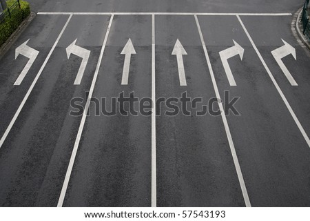 Arrow signs as road markings on a street with six lanes - stock photo