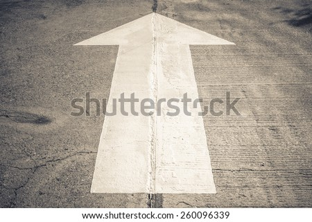 Arrow straight traffic sign on concrete road - stock photo