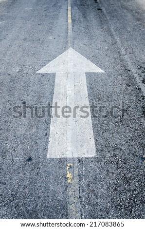 Arrow symbol on a black asphalt road surface - stock photo