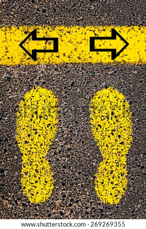 Arrows left and right. Indecision Conceptual image with yellow paint footsteps on the road in front of horizontal line over asphalt stone background. - stock photo