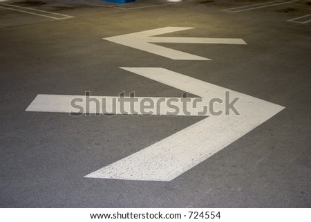 Arrows point the way inside of a city parking structure. - stock photo