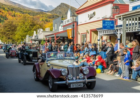 Arrowtown, New Zealand - April 23,2016 : There is a vintage cars parade event during the Arrowtown Autumn Festival on Buckingham Street, people can seen watching and enjoying the parade. - stock photo