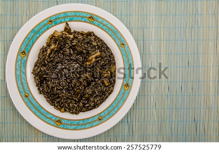 Arroz negro. Black rice. Typical spanish food in mediterranean zone made with rice, onion, tomato, squids and squid ink. Can be eated with alioli sauce - stock photo