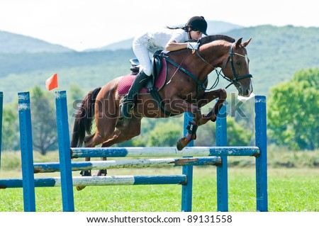 """ARSENEV, RUSSIA - SEPTEMBER 03:  Unidentified rider in action rides horse show jumps at the Riding show """"The Cup of the Governor of the Primorsky Territory, 2011"""" on Sept 03, 2011 in Arsenev, Russia - stock photo"""