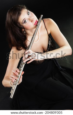 Art and artist. Portrait of woman girl flutist flautist performer playing flute musical instrument on black. Classical music. - stock photo