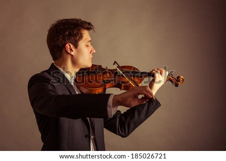 Art and artist. Young elegant man violinist fiddler playing violin on brown. Classical music. Studio shot. - stock photo