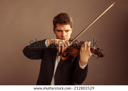 Art and artist. Young elegant man violinist fiddler playing violin on brown. Classical music. Studio shot.