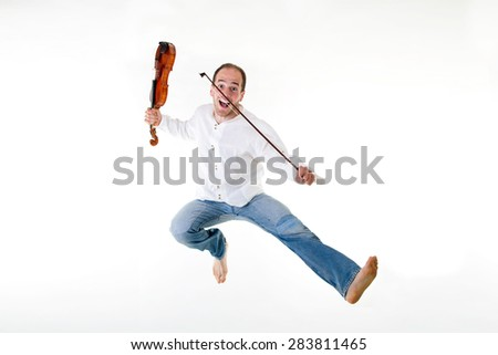 Art and artist. Young man violinist jump with his violin isolated on black background. Classical music. Funny studio shot.
