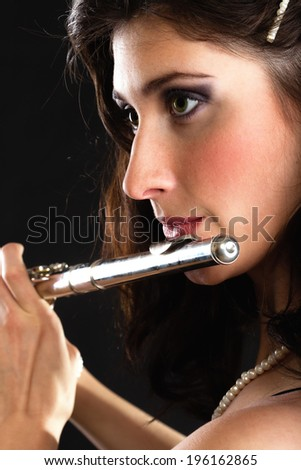 Art and artist. Young woman elegant girl flutist flautist musician perfomrer playing flute musical instrument on black. Classical music. - stock photo