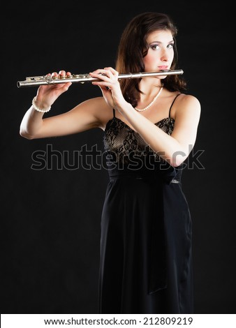 Art and artist. Young woman elegant girl flutist flautist musician performer playing flute musical instrument on black. Classical music. - stock photo