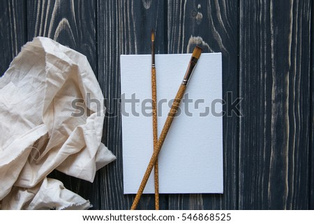 Art and craft tools. Artist's brush, canvas, palette knife on dark rustic background. Space for text.