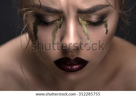 Art beauty close-up portrait of a beautiful model with curly hair. Creative make-up in the style of gold that drain tears from the eyes. - stock photo