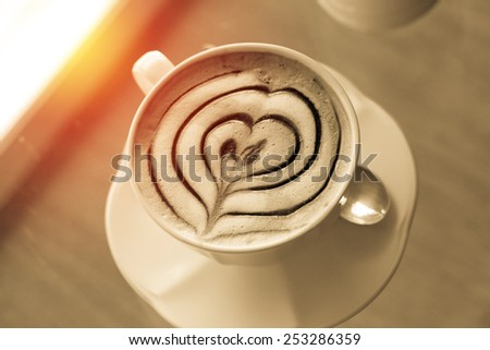 Art cappuccino coffee with heart. Vintage filter. - stock photo