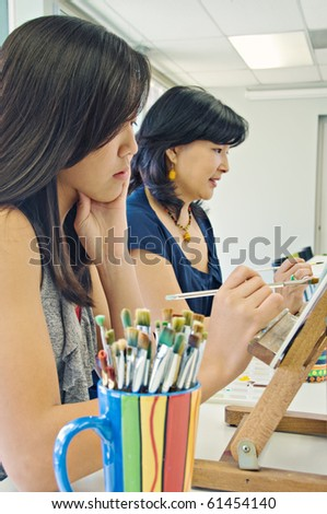 Art class with teen girl and adult - stock photo