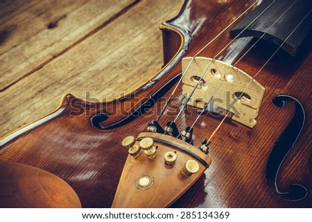 Art. Closeup of old wooden violin stringed instrument on old wooden table. Classical music. - stock photo