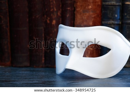 Art concept. Closeup of white classical carnival mask on books background