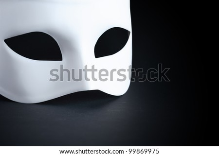 Art concept. Closeup of white mask on black background with free space for text - stock photo