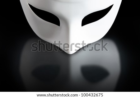 Art concept. Closeup of white mask on black background with reflection - stock photo