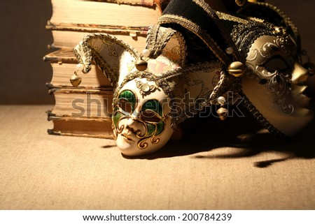 Art concept. Vintage still life with old books near masks - stock photo
