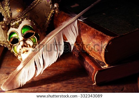 Art concept. Vintage still life with old books near Venetian mask and quill pen - stock photo