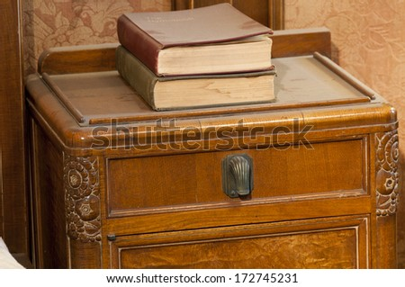 Art deco table with dusty books - stock photo