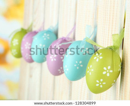 Art Easter background with eggs hanging on fence - stock photo