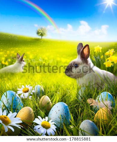 Art Easter bunny rabbit and easter eggs on meadow. - stock photo