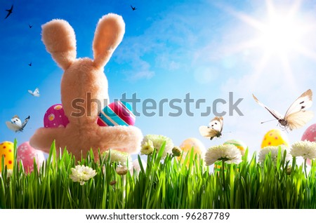 art  Easter teddy bunny and Easter eggs on green grass - stock photo