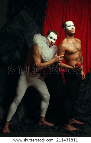 Art fashion concept. Homage to Paul Cezanne's painting Pierrot & Harlequin. Full length portrait of two male mime artists with white masks on faces performing over red & black background. Studio shot - stock photo
