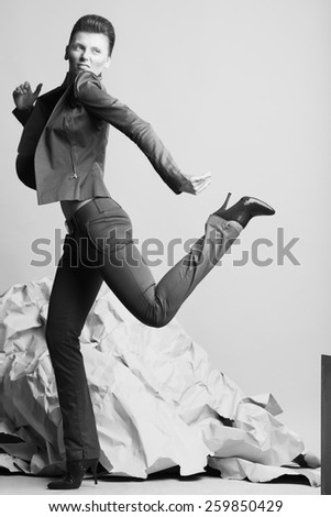 Art fashion concept. Portrait of androgynous model with short hair in casual suit, high heel shoes posing over gray background. Pale skin, natural make-up. David Bowie style. Studio shot - stock photo