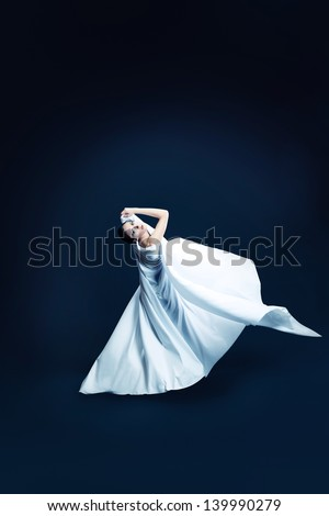 Art fashion photo of a beautiful woman dancing over black background. - stock photo