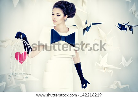 Art fashion photo of a gorgeous woman in paper dress holding birdcage with red heart. Black and white. - stock photo
