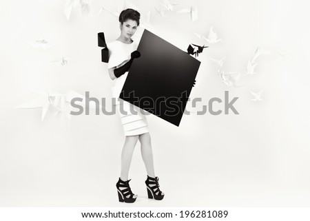 Art fashion photo of a gorgeous woman in paper dress holding black square. Black and white.