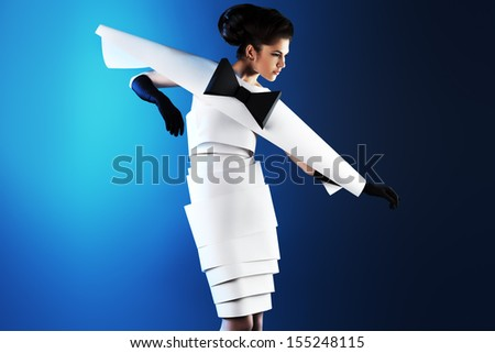 Art fashion photo of a gorgeous woman in paper dress over blue background. Black and white. - stock photo