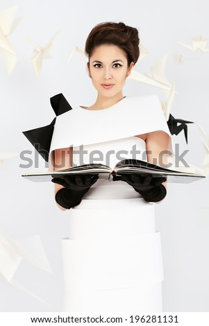 Art fashion photo of a gorgeous woman in paper dress reading a book. Black and white.