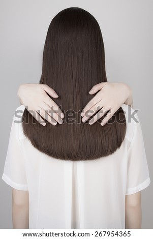 art fashion portrait of women hands on beautiful healthy long hair.back of brunette girl - stock photo