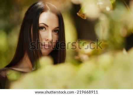 Art fashion portrait of young brunette through leaves. Shallow depth of field - stock photo
