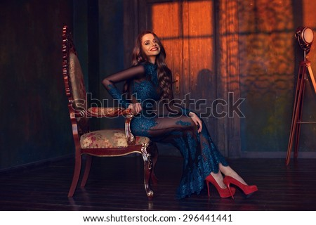 Art fine photo of young elegant beautiful lady wearing long green evening dress with lace and rhinestones and sitting in armchair in interior in sunset lightning.  - stock photo