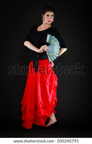 Art. Full length of sexy spanish girl attractive woman in red skirt with fan dancing flamenco traditional dance. - stock photo