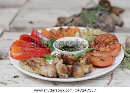 Art grilled vegetables. Grilled vegetables on the white plate. grilled vegetbles on the wooden background. Grilled onion. Grilled tomato. Grilled pepper. grilled mushrooms. Grilled vegetable marrow.  - stock photo