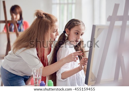 Art Lesson. little girl and woman - stock photo