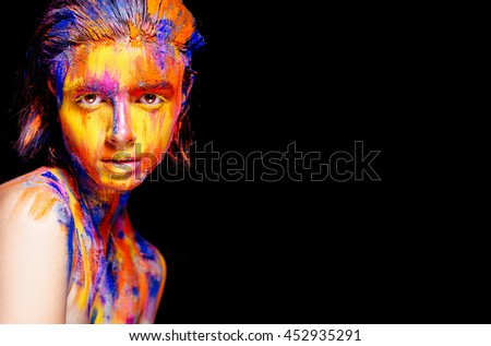 Art makeup. Face, neck and hair girls smeared with bright colors of yellow, blue and pink colors. Holi Festival
